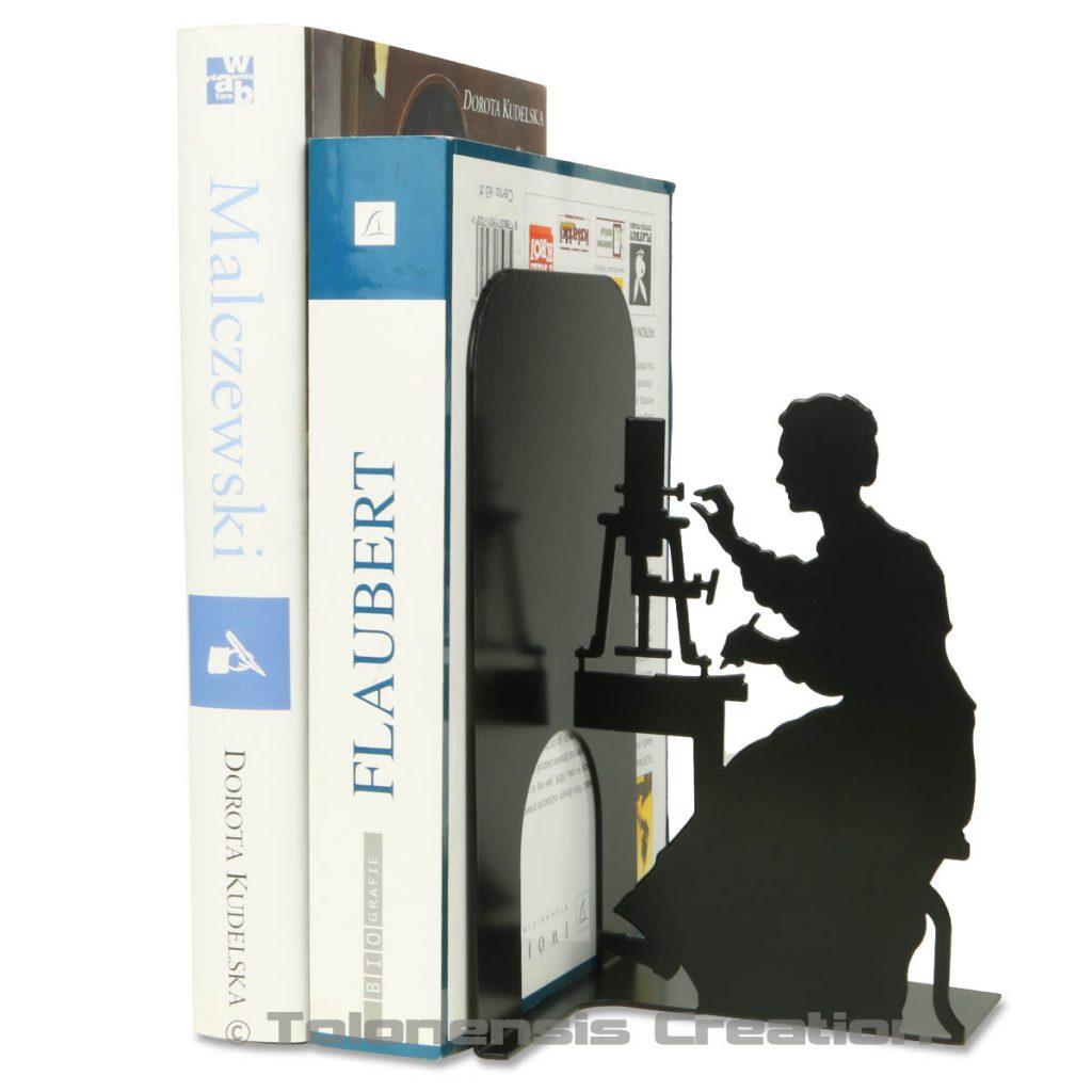 Serre-livres Marie Curie manipulant l'électromètre piézoélectrique mis au point par Pierre Curie
